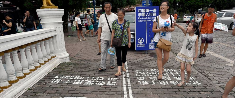 """PHOTO: Residents look at a sign with the words """"Chinas First Cellphone Lane"""" explaining the use of a lane which separates those using their phones as they walk from others in Chinas Chongqing Municipality, Sept. 13, 2014."""