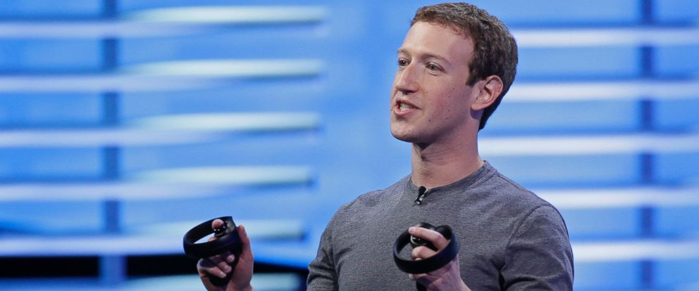 Facebook CEO Mark Zuckerberg holds a pair of virtual reality handsets during the keynote address at the F8 Facebook Developer Conference, April 12, 2016, in San Francisco.