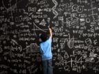 PHOTO: A young boy writes math equations on chalkboard.
