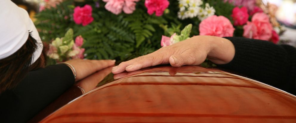 PHOTO: Mourners place their hands on the casket at a funeral in this undated file photo