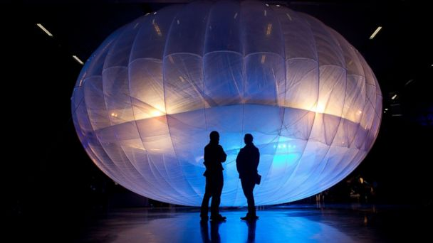 PHOTO: Visitors stand next to a high altitude WiFi internet hub, a Google Project Loon balloon, on display at the Airforce Museum in Christchurch in this June 16, 2013, file photo.