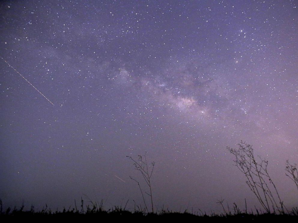 PHOTO: This long-exposure photograph taken on Earth Day shows the Lyrids meteor shower passing near the Milky Way in the clear night sky of Thanlyin, nearly 14 miles away from Yangon on April 23, 2015.
