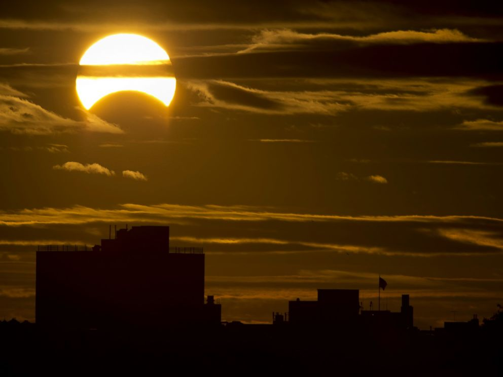 PHOTO: A partial Solar eclipse is seen just after sunrise over the Queens borough of New York across the East River, Nov. 3, 2013.