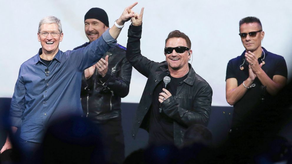 Apple CEO Tim Cook, left, greets the crowd with U2 during an Apple special event at the Flint Center for the Performing Arts, Sept. 9, 2014, in Cupertino, California.