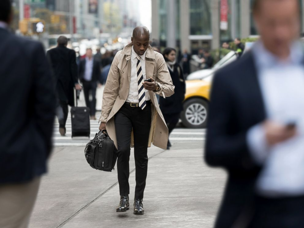 PHOTO: People walk and text while crossing the street.