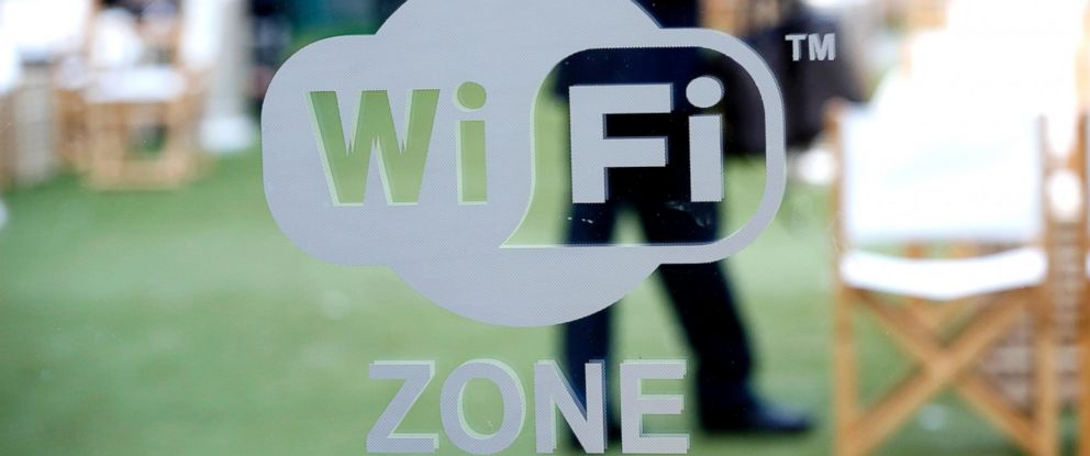 PHOTO: Visitors are seen in a cafe area behind a sign indicating a free WiFi zone at Mobile World Congress in Barcelona, Feb. 27, 2013.