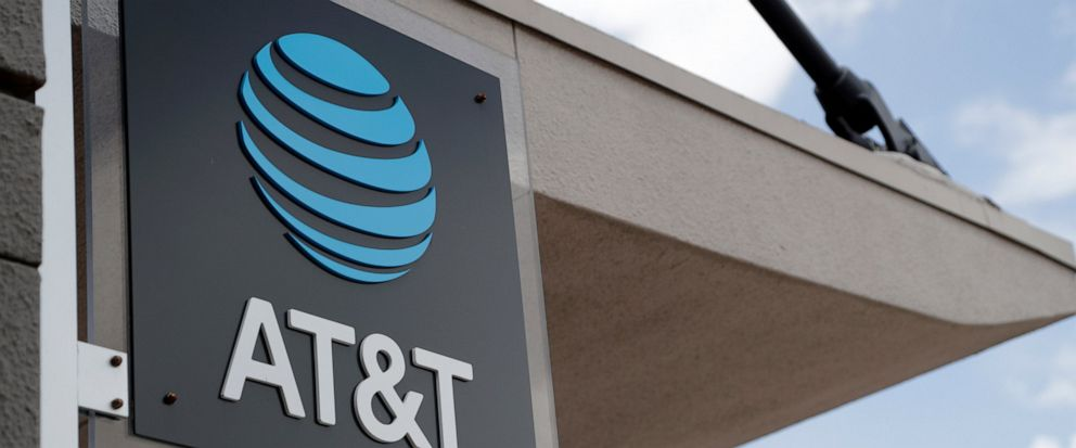 FILE - In this July 18, 2019, file photo, a sign is displayed at an AT&T retail store in Miami. Activist hedge fund manager Elliott Management is making a new $3.2 billion investment in AT&T, saying the company could be valued at more than $60 a shar