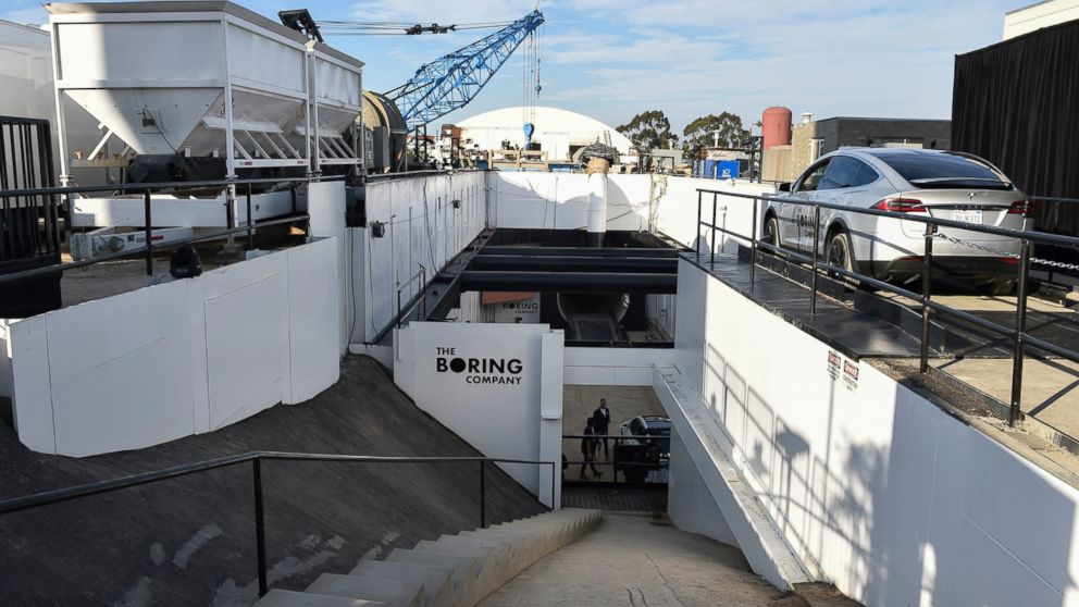 """A modified Tesla Model X rests on an elevator, right, above the pit and tunnel entrance before an unveiling event for the Boring Company Hawthorne test tunnel in Hawthorne, Calif., on Tuesday, Dec. 18, 2018. Elon Musk unveiled his underground transportation tunnel on Tuesday, allowing reporters and invited guests to take some of the first rides in the revolutionary albeit bumpy subterranean tube — the tech entrepreneur's answer to what he calls """"soul-destroying traffic."""" (Robyn Beck/Pool Photo via AP)"""