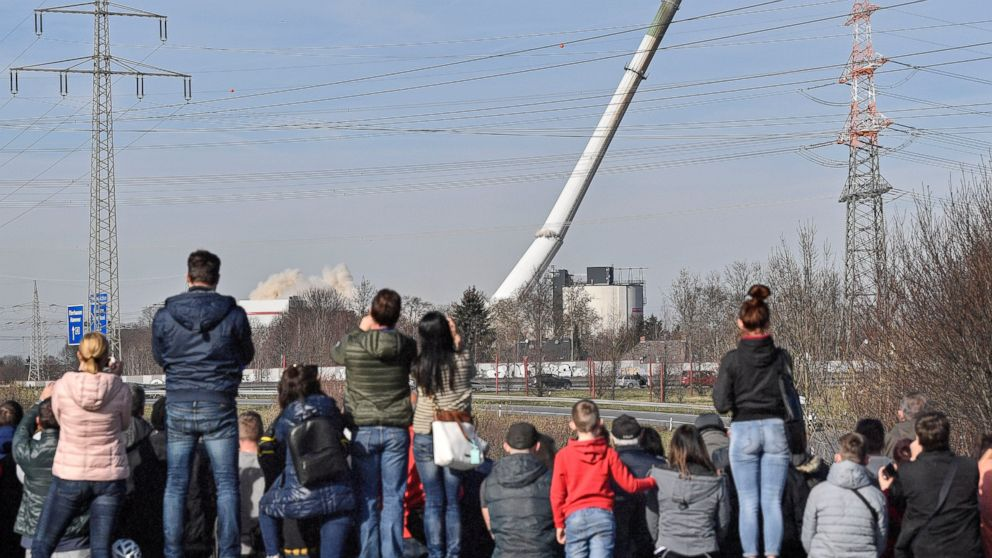 People watching the fall of a chimney during the blasting of a former coal-fired power station in Dortmund, Germany, Sunday, Feb. 17, 2019. (AP Photo/Martin Meissner)