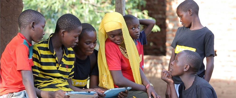 In this undated photo provided by XPRIZE, children in a village in the Tanga region of Tanzania gather to learn from tablets using open-sourced software that would easily be downloaded by illiterate children to teach themselves to read. Thats what n