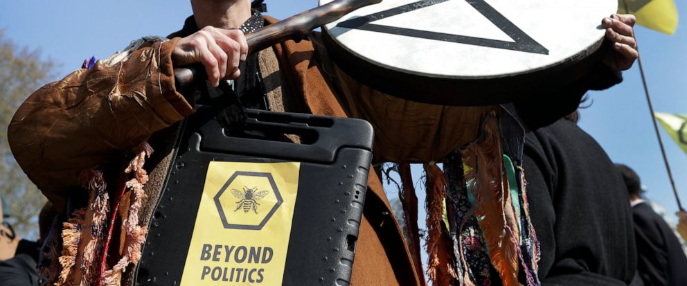 A demonstrator bangs a drum during a climate protest in Parliament Square in London, Monday, April 15, 2019. Extinction Rebellion have organised a nationwide week of action, they are calling for a full-scale Rebellion to demand decisive action from g