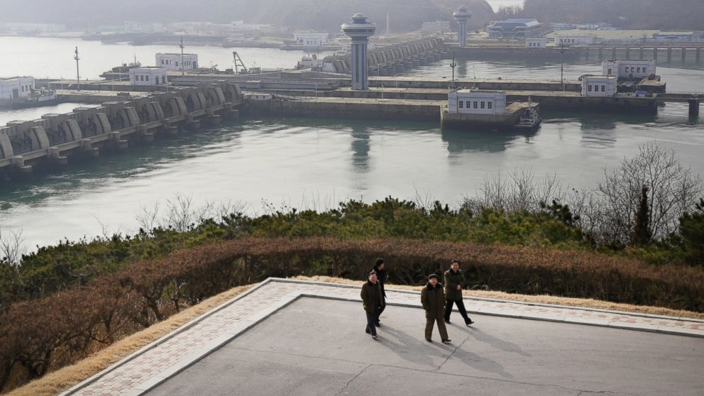 In this Feb. 2, 2019, photo, North Koreans men walk with the background of the West Sea Barrage in Nampo, North Korea. North Korea is exploring two ambitious alternative energy sources, tidal power and the production of coal-based synthetic fuels, that could greatly improve its standard of living while reducing its reliance on oil imports and vulnerability to sanctions. (AP Photo/Dita Alangkara)