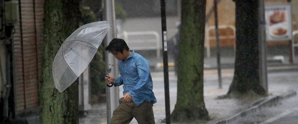 A man crosses the road in Hamamatsu, central Japan, Saturday, Oct. 12, 2019. A heavy downpour and strong winds pounded Tokyo and surrounding areas on Saturday as a powerful typhoon forecast as the worst in six decades approached landfall, with street