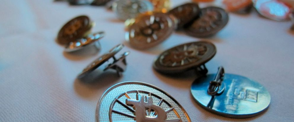 FILE-In this Feb. 12, 2014 file photo Bitcoin buttons are displayed on a table at the Inside Bitcoins conference in Berlin. Researchers calculate that the electricity required for the virtual currency bitcoin generates as much carbon dioxide as citie