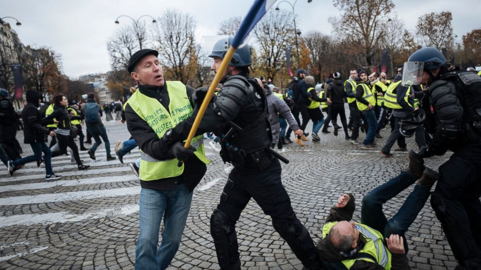 "FILE - In this Nov. 24, 2018, file photo, Herve Ryssen, left, close to the ultra-right and convicted for antisemitic and racist comments, wearing a yellow jacket, clashes with riot police officers on the Champs-Elysees avenue in Paris. The offer by Italy's 5-Star Movement to share its web platform with France's ""yellow vests"" could be harbinger of what's to come in the upcoming European Parliament elections. The French movement has brought together left and right extremes within France. (AP Photo/Kamil Zihnioglu, File)"