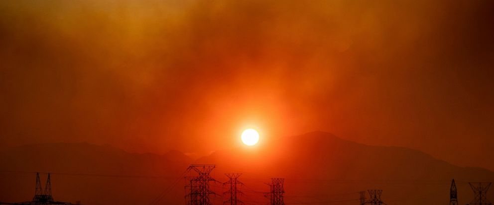 Smoke from the Saddleridge Fire hangs above power lines as the sun rises in Newhall, Calif., on Friday, Oct. 11, 2019. An aggressive wildfire in Southern California seared its way through dry vegetation Friday and spread quickly, destroying more than