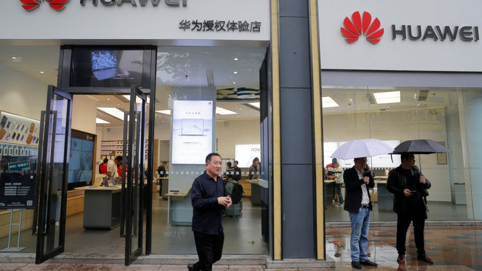 People walk past a Huawei retail shop in Shenzhen, China's Guangdong province, Thursday, March 7, 2019. Chinese tech giant Huawei is challenging a U.S. law that labels the company a security risk and would limit its access to the American market for telecom equipment. (AP Photo/Kin Cheung)