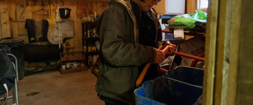 In this Friday, April 5, 2019, photo, Kelly Povroznik grabs a few carrots from inside her storage space to give to her horses in their pasture outside of Clarksburg, W.Va. Povroznik teaches an online college course that has been hampered by slow conn