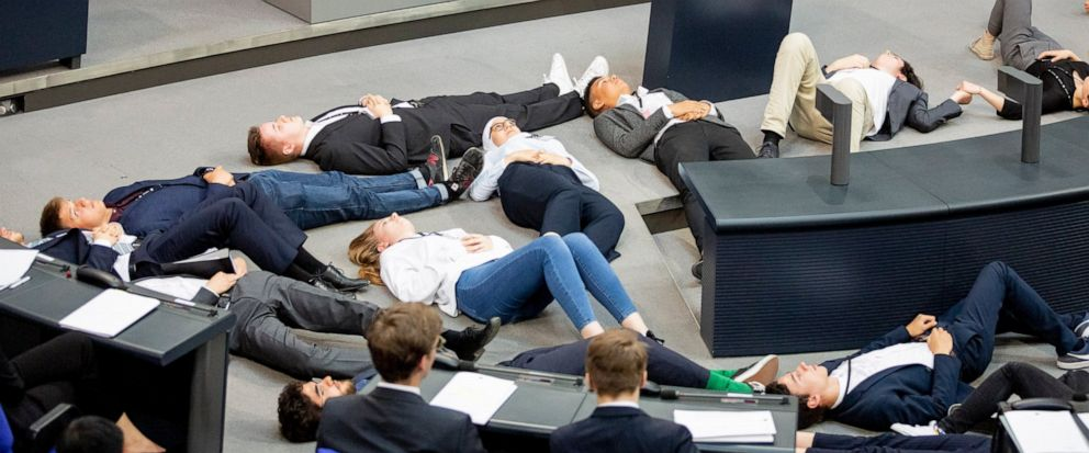 "Participants of a protest action for climate justice by Fridays For Future lie on the floor in the plenary hall of the Bundestag in Berlin, Germany, Tuesday, June 4, 2019. In the simulation game ""Youth and Parliament"", young people slip into the role"