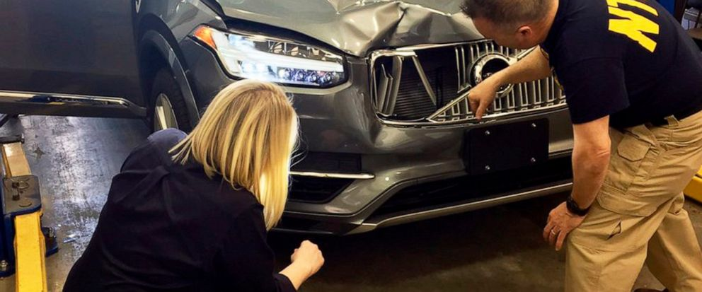 FILE - In this March 20, 2018, file photo, provided by the National Transportation Safety Board, investigators examine a driverless Uber SUV that fatally struck a woman in Tempe, Ariz. Police outside Phoenix recently closed part of a street to conduc