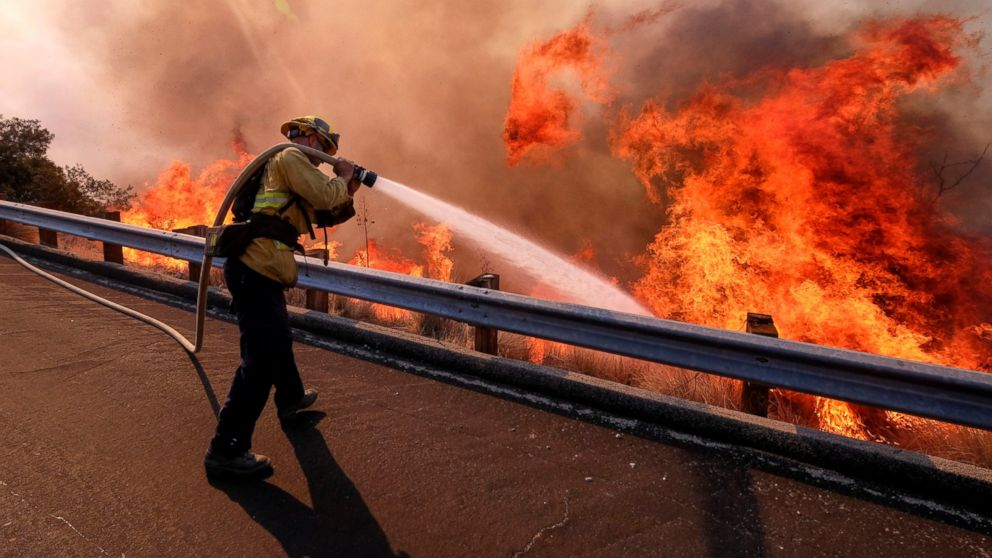 In this Nov. 12, 2018 file photo a firefighter battles a fire along the Ronald Reagan Freeway, aka state Highway 118, in Simi Valley, Calif. A group of U.S. senators from around the American West sent a letter to President Trump warning that firefighting academies that provide required annual training for thousands of front-line fire crews are canceling classes because their federally employed instructors are on furlough. (AP Photo/Ringo H.W. Chiu, File)