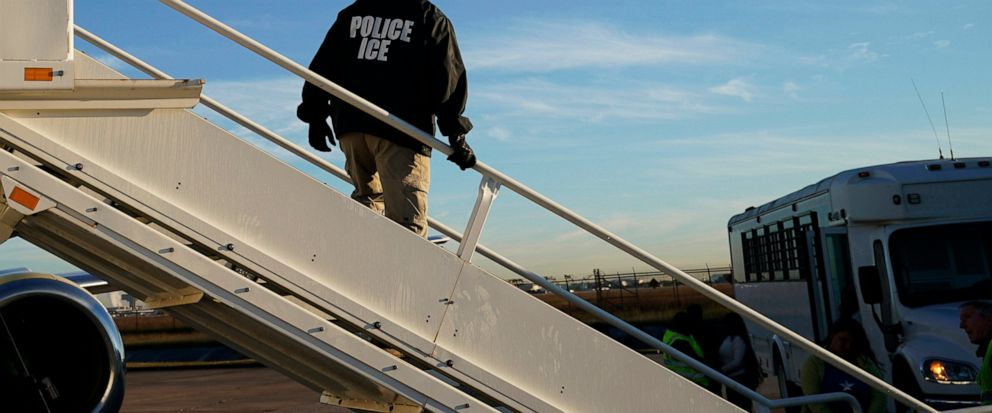 FILE - In this Nov. 16, 2018, file photo, an officer watches as immigrants who entered the United States illegally are deported on a flight to El Salvador by U.S. Immigration and Customs Enforcement in Houston. Civil rights activists complained Monda