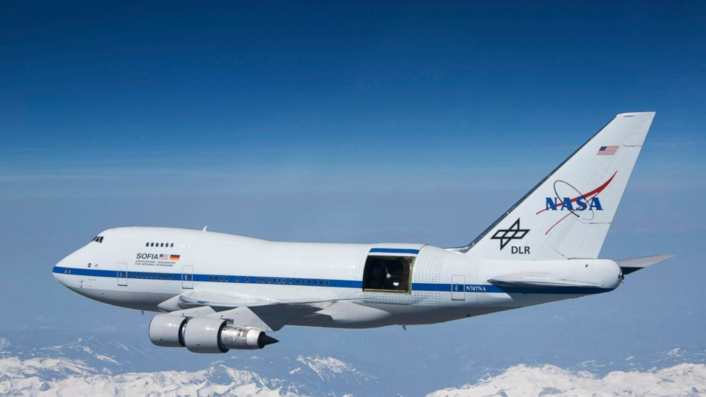 """This undated photo provided by NASA shows SOFIA over the snow-covered Sierra Nevada mountains with its telescope door open during a test flight. The world's largest airborne observatory was supposed to be parked in Seattle this week, so thousands of scientists attending the """"Super Bowl of Astronomy"""" could behold this marvel: a Boeing 747, like this one shown, for example, outfitted with a massive telescope used to study the fundamental mysteries of the universe. (Jim Ross/NASA via AP)"""