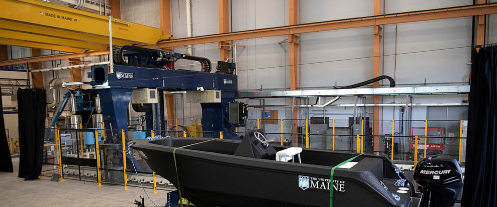 In this Wednesday, Oct. 9, 2019 photo provided by the University of Maine, a 25-foot, 5,000-pound patrol boat, center, that was produced using a large polymer 3D printer, behind left, rests on a trailer on the schools campus, in Orono, Maine. The bo
