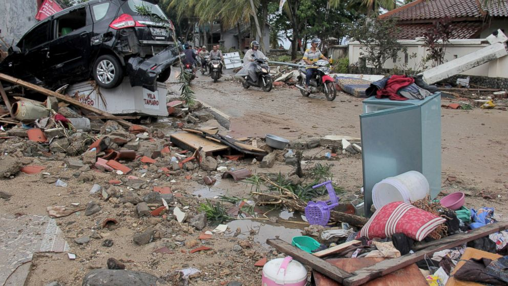 Motorists ride past debris following a tsunami in Anyar, Indonesia, Sunday, Dec. 23, 2018. An eruption of one of the world's most infamous volcanic islands is believed to have triggered a tsunami that killed hundreds of people in Indonesia during a busy holiday weekend. The waves smashed onto beaches at night without warning, ripping houses and hotels from their foundations in seconds and sweeping terrified concertgoers into the sea. (AP Photo)