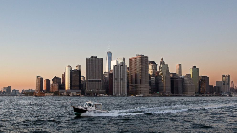 FILE - In this Oct. 19, 2017 file photo, a boat crosses New York Harbor in front of the Manhattan skyline. Mayor Bill de Blasio is announcing a plan, Thursday, March 14, 2019, to protect lower Manhattan from rising sea levels by surrounding it with earthen berms and extending its shoreline by as much as 500 feet. (AP Photo/Mark Lennihan, File)