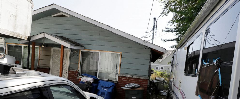 "FILE - In this July 31, 2019, file photo vehicles are parked outside the home of Paige A. Thompson, who uses the online handle ""erratic,"" in Seattle. Thompson, of Seattle, was arrested last month after the FBI said she obtained personal information f"