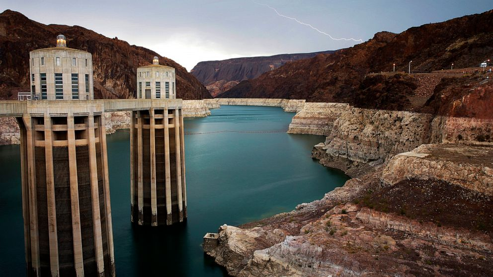 FILE - In this July 28, 2014, file photo, lightning strikes over Lake Mead near Hoover Dam that impounds Colorado River water at the Lake Mead National Recreation Area in Arizona. The Bureau of Reclamation is forecasting first-ever water shortages be