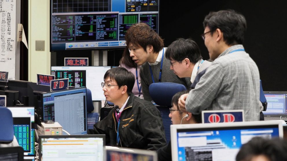In this photo provided by the Japan Aerospace Exploration Agency (JAXA), staff of the Hayabusa2 Project watch monitors for a safety check at the control room of the JAXA Institute of Space and Astronautical Science in Sagamihara, near Tokyo, Thursday, Feb. 21, 2019. Japanese spacecraft Hayabusa2 is approaching the surface of the asteroid Ryugu about 280 million kilometers (170 million miles) from Earth. JAXA said Thursday that Hayabusa2 began its approach at 1:15 p.m. (ISAS/JAXA via AP)