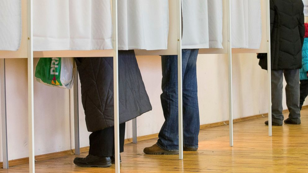 FILE - In this file photo dated Sunday, March 1, 2015, people fill their ballot papers in voting booths at a polling station in Tallinn, Estonia. Estonia has moved away from traditional balloting, with online voting starting Thursday Feb. 21, 2019, for next month's general election, amid tight protective measures. (AP Photo/Liis Treimann, FILE)