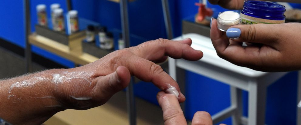 FILE - In this Aug. 29, 2018, file photo, a customer tries a free sample of a pain cream that contains cannabidiol (CBD) for her arthritis at Minnesota Hempdropz in Maplewood, Minn. Mainstream retailers are leaping into the world of products like ski