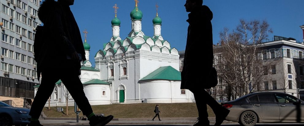People are silhouetted as they walk along an avenue past an old Orthodox church in the background in Moscow, Russia, Tuesday, April 2, 2019. (AP Photo/Alexander Zemlianichenko)