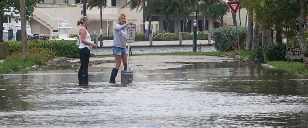 "FILE - In this Oct. 5, 2017, file photo, residents move a ""no wake,"" sign through flood waters caused by king tides in Fort Lauderdale, Fla. Federal scientists, according to a report released Wednesday, July 10, 2019, predict 40 places in the U.S. wi"