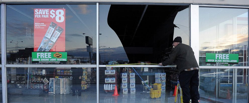 FILE - In this Nov. 30, 2018, file photo, Dennis Keeling, of Instant Services, measures for a broken window at an auto parts store following an earthquake in Anchorage, Alaska Seven weeks after the massive earthquake struck Alaska, the seemingly endl