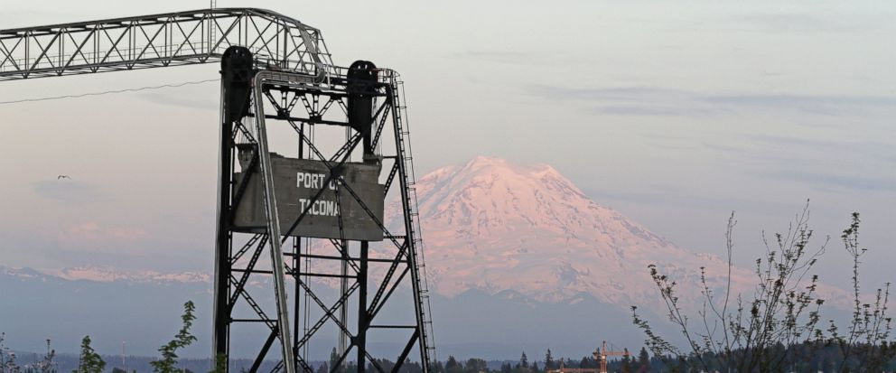 In this May 7, 2018 photo, Mount Rainier is seen at dusk behind the Murray Morgan Bridge in downtown Tacoma, Wash. The eruption of the Kilauea volcano in Hawaii has geologic experts along the West Coast warily eyeing the volcanic peaks in Washington,