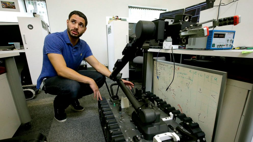 In this Aug. 28, 2018 photo, software engineer Nicholas Otero, of Woburn, Mass., speaks with a colleague about features on a Centaur robot, right, at Endeavor Robotics in Chelmsford, Mass. The Army is looking for a few good robots. These robots won't fight, at least not yet. But they will be designed to help the men and women who do. The companies making them are waging a different kind of battle. At stake is a contract worth almost half a billion dollars for 3,000 backpack-sized robots that can defuse bombs and scout enemy positions. (AP Photo/Steven Senne)