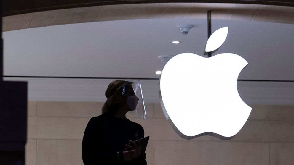 FILE - In this Feb. 5, 2021, file photo, an Apple store employee wears personal protective equipment in New York. At an event on Monday, June 7, 2021, Apple unveiled a variety of incremental improvements to the software that powers iPhones, iPads and