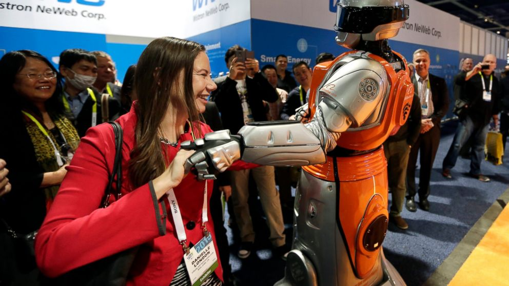 FILE- In this Jan. 6, 2015, file photo Danielle London, left, dances with a performer dressed as a robot at the Alibaba.com booth at the International CES in Las Vegas. The CES 2019 gadget show, which kicks off Sunday, will showcase the expanding influence and sway of China's rapidly growing technology sector. Chinese tech giants like Baidu and Alibaba have made flashy presentations at CES in recent years. Roughly 40 percent of all exhibitors planning to showcase their latest technology at this week's Las Vegas event are Chinese firms, second only to the U.S. in sheer numbers. (AP Photo/Jae C. Hong, File)