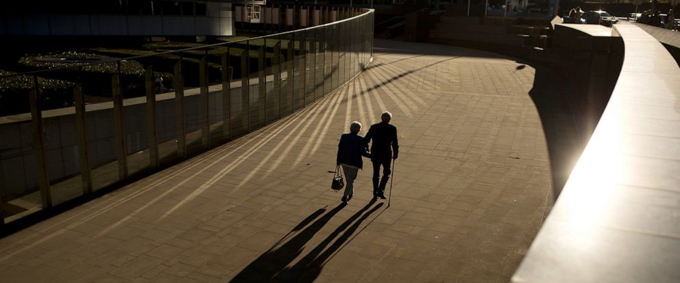 FILE - In this Thursday, Sept. 27, 2018 file photo, an elderly couple walks past the Berlaymont building, the European Commission headquarters, in Brussels. Research released on Sunday, July 14, 2019 suggests that a healthy lifestyle can cut the risk