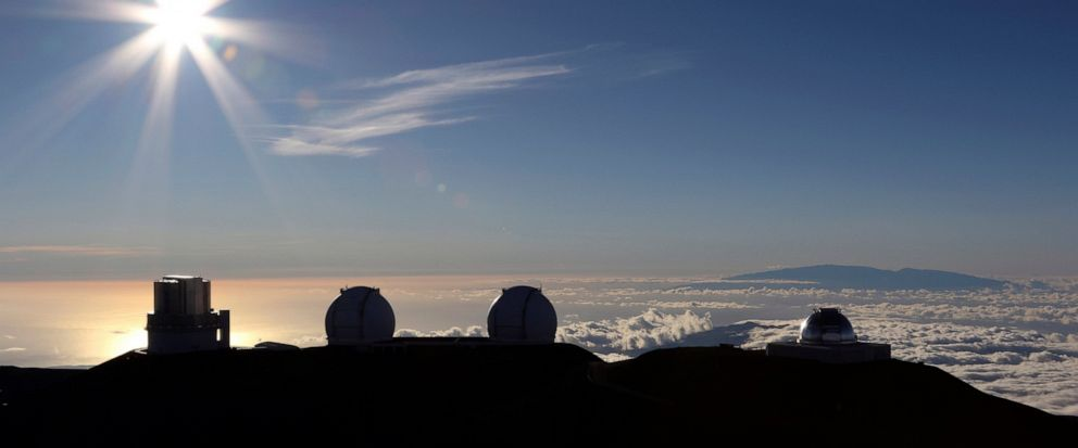 FILE - In this July 14, 2019, file photo, the sun sets behind telescopes at the summit of Mauna Kea. A senior University of Hawaii official says losing the Thirty Meter Telescope could mean losing billions of dollars in research funding over the next