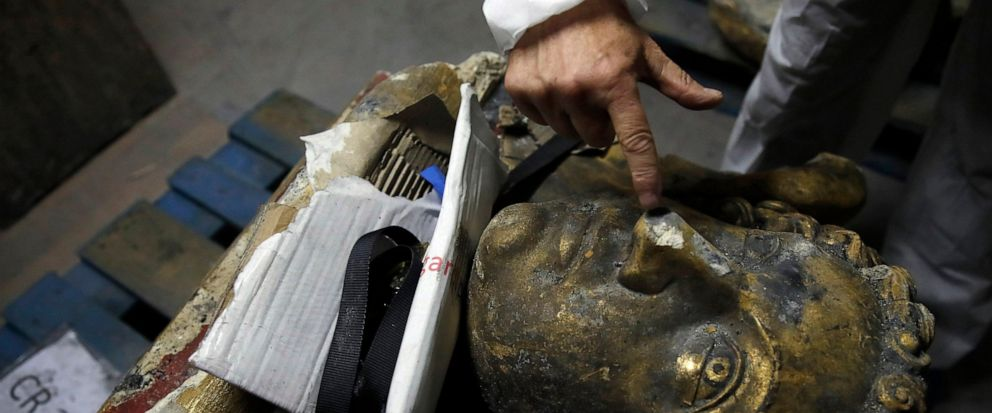 In this photo taken on Wednesday, Oct. 9, 2019, stone expert Jean-Didier Mertz, shows a broken nose of the golden angel that was once atop Notre Dame cathedral, in a warehouse at Champs-sur-Marne, west of Paris. Scientists at the French governments