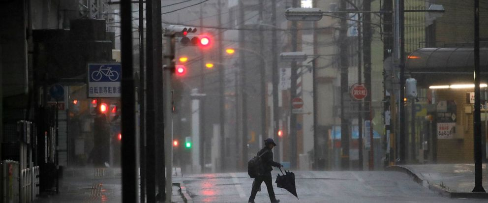 A woman crosses the road in Hamamatsu, central Japan, Saturday, Oct. 12, 2019. A heavy downpour and strong winds pounded Tokyo and surrounding areas on Saturday as a powerful typhoon forecast as the worst in six decades approached landfall, with stre