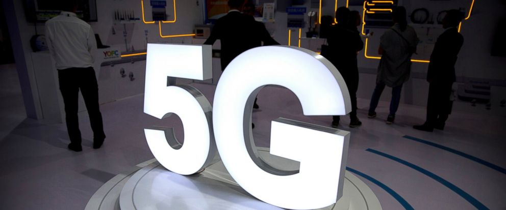 FILE- In this Sept. 26, 2018, file photo visitors stand near a 5G logo at a display the PT Expo in Beijing. A handful of Verizon customers will soon have faster wireless service, but they'll have to pay $10 a month more. Verizon says it'll flip the s