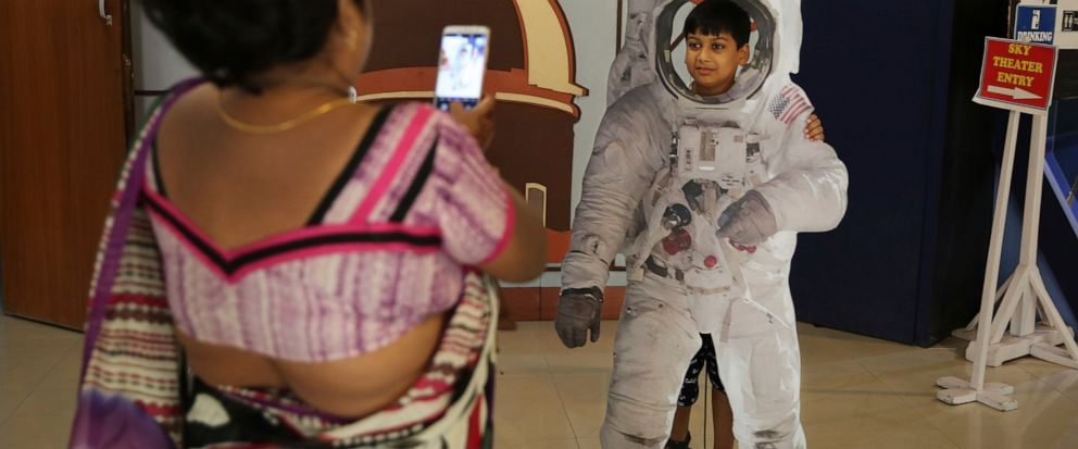 An Indian woman takes a photograph of her son as he poses in a cut-out of an astronaut at the Nehru Planetarium in New Delhi, India, Thursday, July 11, 2019. India is looking to take a giant leap in its space program and solidify its place among the