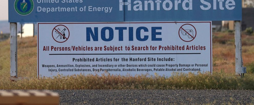 FILE - In this May 9, 2017, file photo, signs are posted at an entrance to the Hanford Nuclear Reservation in Richland, Wash.The state of Washington believes the federal government is unlikely to meet legal deadlines for emptying underground tanks ho