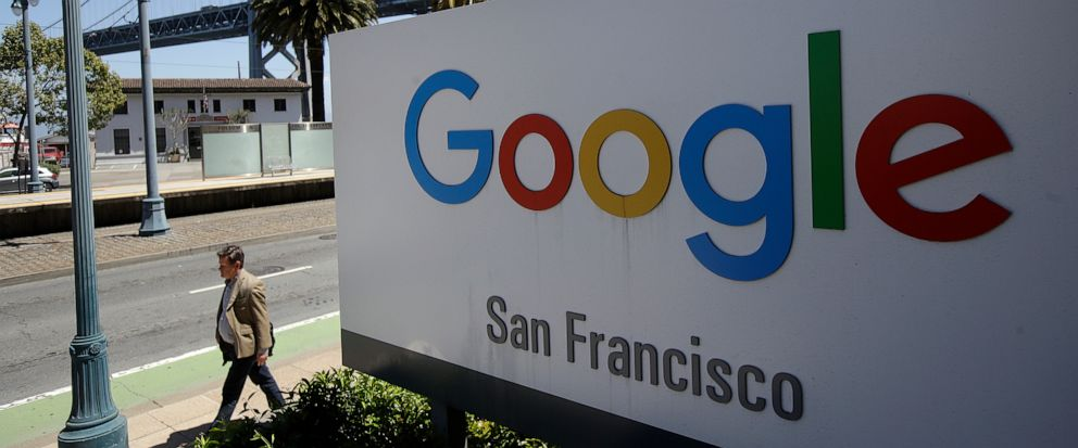 FILE - In this May 1, 2019, file photo a man walks past a Google sign outside with a span of the Bay Bridge at rear in San Francisco. A group of states are expected to announce an investigation into Google on Monday, Sept. 9, to investigate whether t
